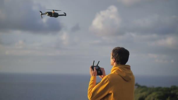 Reisender fotografiert oder filmt per Drohne. Männchen lernen fliegen und drehen unterwegs Videos mit einem Drohnen-Quadrocopter. Modernes Hobbykonzept