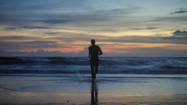 Silhouette of handsome muscular man running at dusk against sunset against the background of ocean waves