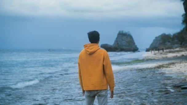 Az ember felemeli a kezét a gyönyörű trópusi strandon állva esténként. Szabadság koncepció. Életfogytiglan, kihívás.