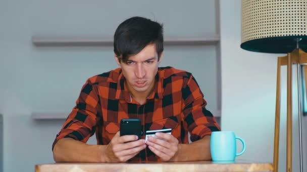 Junger Mann kauft online mit Telefon und Kreditkarte und fühlt sich getäuscht. Erfolglose Interneteinkäufe. Kreditkartenbetrug, Kontosperrung, Kontensperrung.