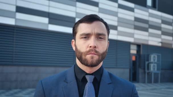 Portrét pohledný vousatý podnikatel muž v obleku stojí v blízkosti moderní kancelářské budovy