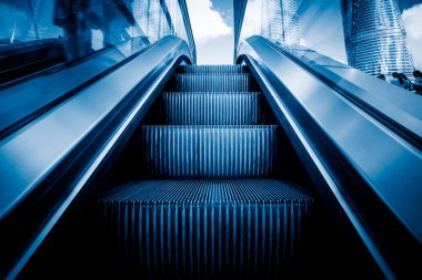 Escalator in an underground station in blue tone.