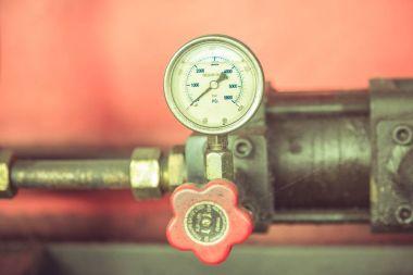 Pressure gauge on metal pipes at industry