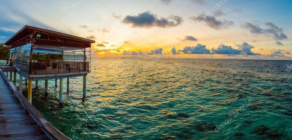 Sunset on Maldives island, water villas resort from the ocean view.
