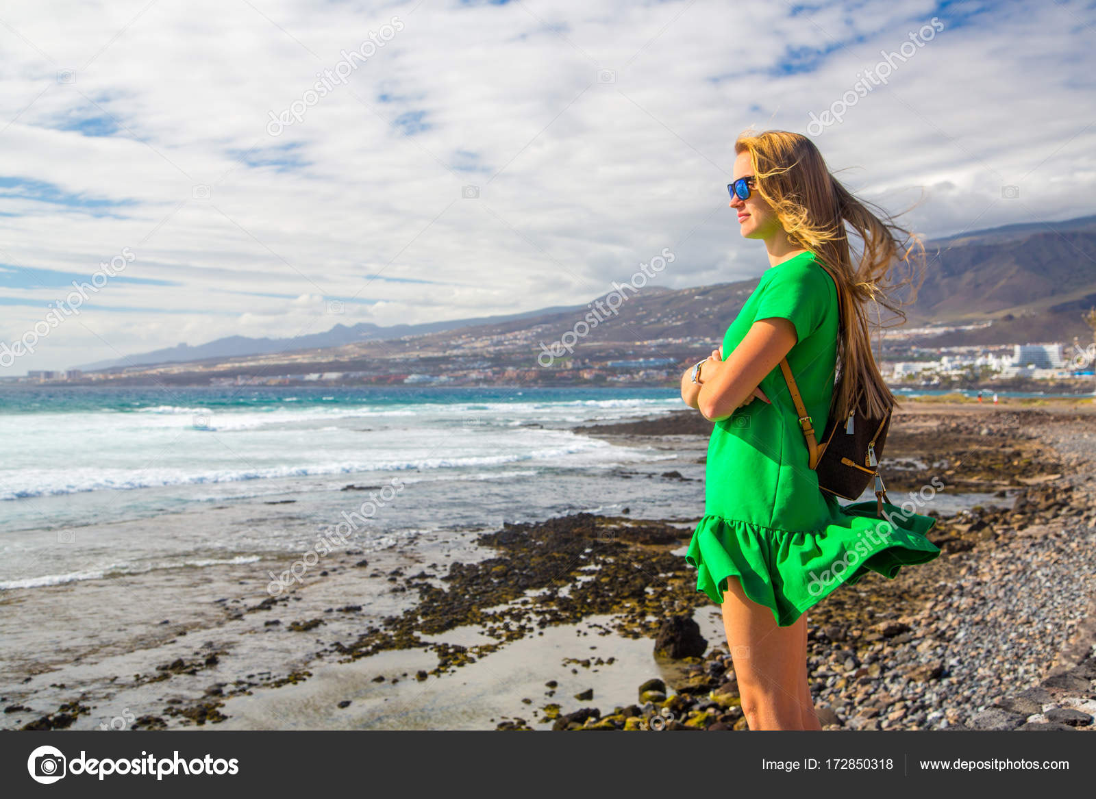 eaaf84062f Young girl standing on the edge of the ocean on Tenerife island. Looking  into the horizon.