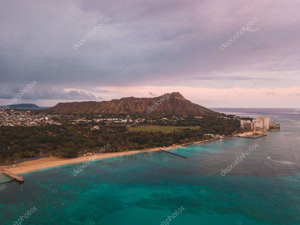 Beautiful Waikiki beach purple sunset. Absolutely amazing aerial view on the Hawaii island with a Diamond head crater and Honolulu city skyline view.