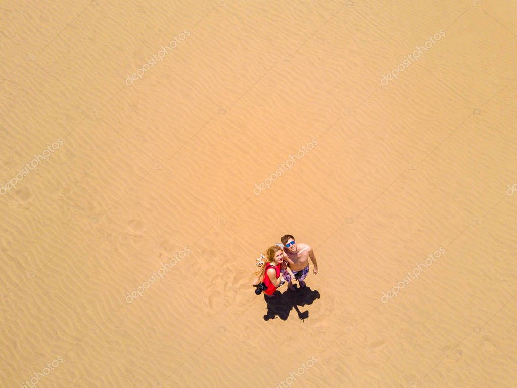 Aerial view of young couple kissing in a desert from above. Maspalomas dunes in Gran Canaria, Spain.