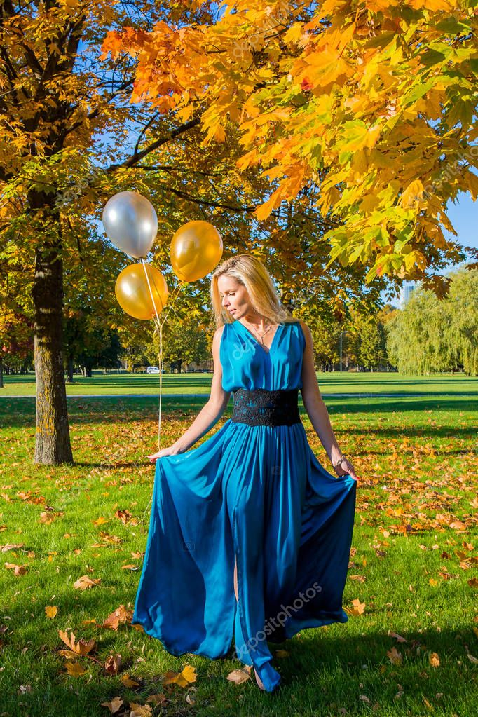 Beautiful young sexy lady in a dress standing in the park during golden autumn season with balloons in her hands