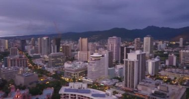Amazing aerial evening view of the Waikiki beach in Honolulu with surfers surfing in the Pacific ocean.