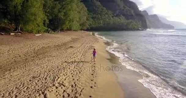 A légi felvétel a szép lány fut le a Na Pali tengerparton, Hawaii Kauai szigeten