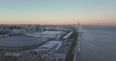 Amazing sunset view over Lisbon town by the cable car and modern stadium arena.