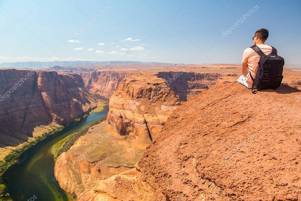 Young man sitting by the edge of the cliff. Amazing view at the Horse Shoe Bend at the Grand Canyon.