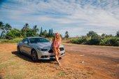 Kauai, Havaj, Usa – 10. srpna 2017: Mladá krásná dáma stojící stříbrný Ford Mustang na ostrově mezi dlaněmi do oceánu
