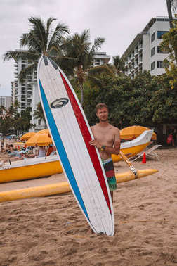 Young man surfer standing on the Waikiki beach in Hawaii with a surf board ready to go surfing. Honolulu, USA. August 30, 2017.