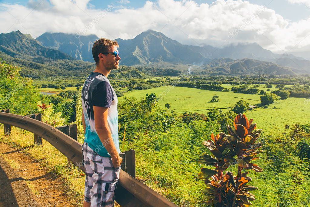 Young man standing by the side of the road watching an amazing nature on the island of Kauai, Hawaii, USA. August 30, 2017.