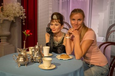Girl sitting by the Audrey Hepburn wax figure at Madame Tussauds in Sydney Australia as on 17 Jan 2017