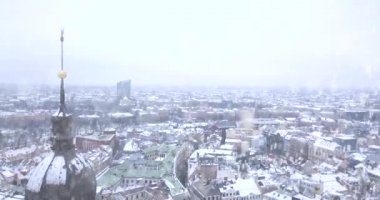 Aerial view over Riga old town (Vecriga) in winter during heavy snow. White Riga from above. Amazing panoramic view. Flying over old town by the golden rooster.