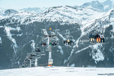 Davos, Switzerland. January 10, 2019. Mountain ski lift with seats going over the mountain and paths from skies and snowboards stock vector