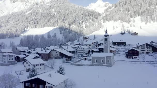 Panoramablick auf wunderschöne Winterlandschaft in den Schweizer Alpen mit Wallfahrtskirche und kleiner Winterstadt inmitten mächtiger Berge.