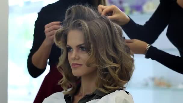 Kadeřnice dělá vlasy krásná dívka šaty v salonu krásy