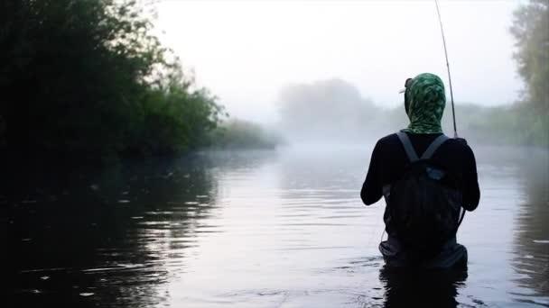 Muškaření v řece ráno jde rybář