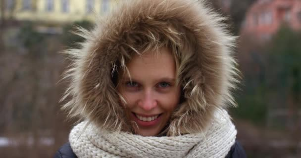 young beautiful girl in winter jacket with fur hood outdoor