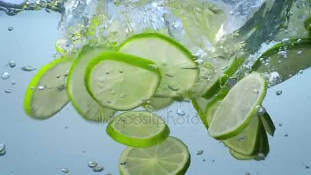 frische Kalkscheiben fallen ins Wasser und treiben mit Blasen in Zeitlupe.