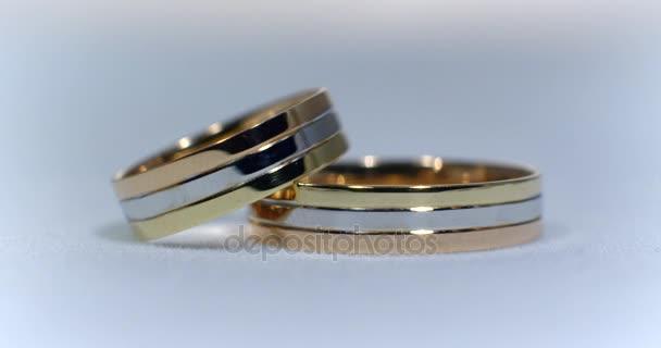 Due anelli di nozze doro che si trova sul bianco-grigio brillante superficie con luce close up closeup. Trasfusione di luce sugli anelli