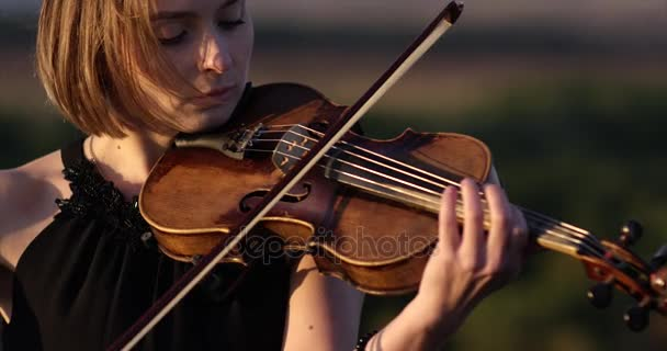 Girl violinist playing the violin on the roof with sky background.