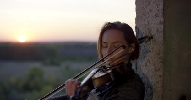 Playing violin in ruined building with sunset 4K.