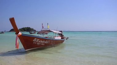 Thai traditional wooden boat with ribbon decoration at ocean shore under blue sky.Thailand tropical beach landscape, Lipe Island