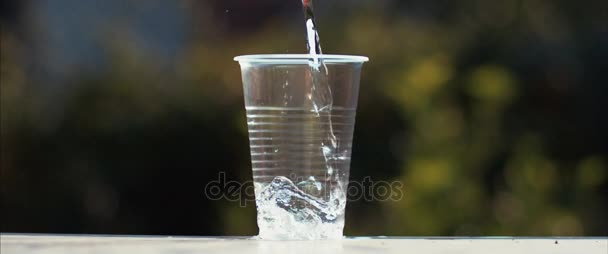 Acqua che scorre nel bicchiere di plastica. Refrigeratore dacqua. Primo piano della mano che tiene la tazza con lacqua. Acqua minerale di versamento in overflow e tazza trasparente
