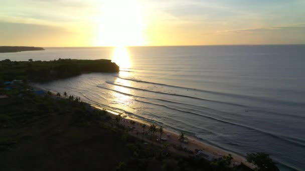 Aerial view of beautiful beach coast during sunset with surfers riding waves.