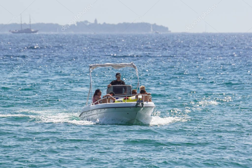 Nice , France - 10 august 2017 : a man drives his boat back into the harbor or a ride to the sea during a hot summer day .