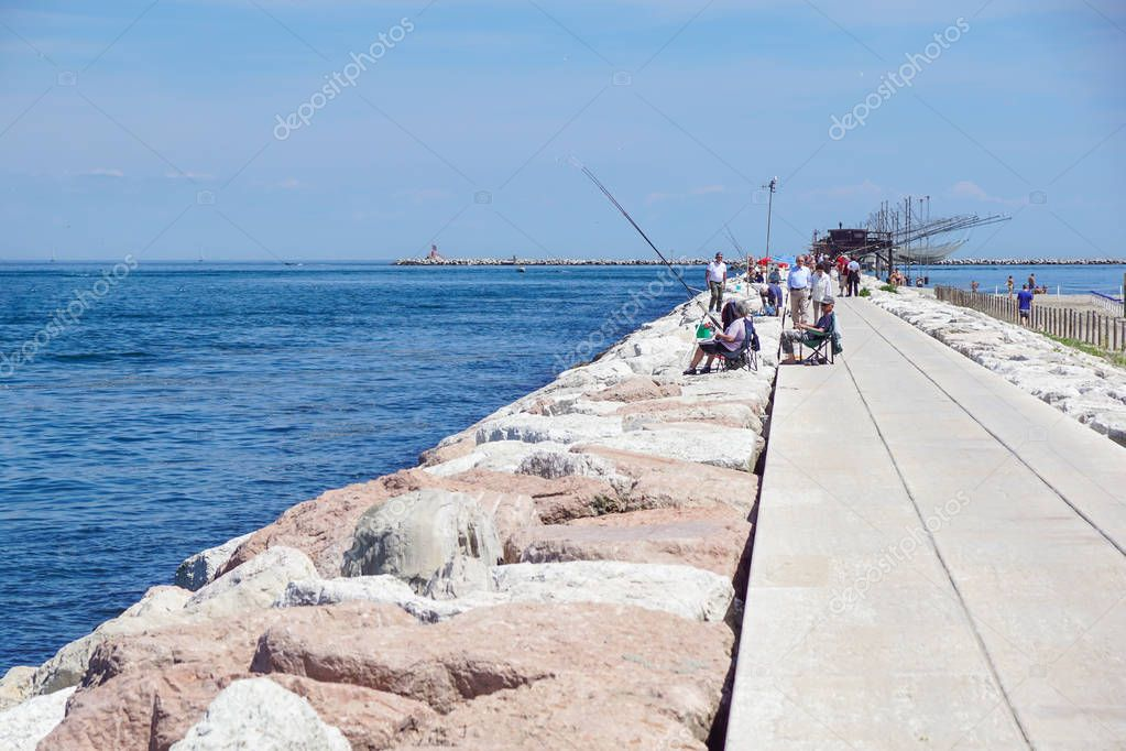 Venice , Italy 8 July 2017 : Tourists fish and relax on the dock at the entrance to the sea in Europe