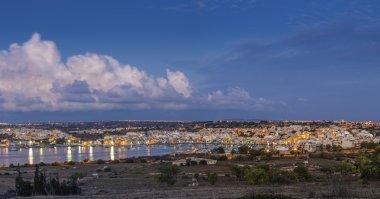 Marsaxlokk, Malta - Panoramic skyline view of Marsaxlokk, the traditional fisherman village of Malta at sunrise with blue sky and beautiful clouds