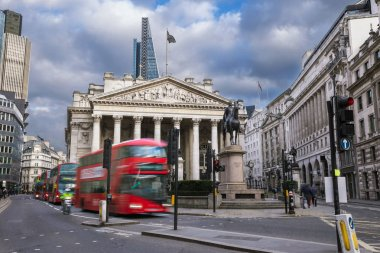 London, England - The Royal Exchange building with moving red double decker bus