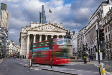 London, England - The Royal Exchange building with moving red double decker bus on the move
