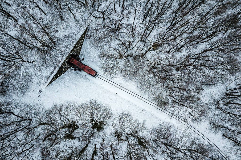Budapest, Hungary - Aerial view of snowy forest with red train coming out of a tunnel at winter time, captured from above with a drone at Huvosvolgy