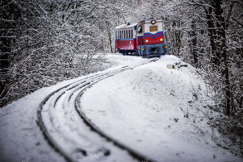 Budapest, Hungary - Beautiful winter forest scene with snow and old colorful train on the track in the Hungarian woods of Huvosvolgy
