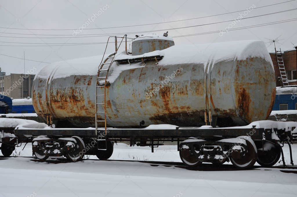 Detailed photo of snowy frozen railway freight car. A fragment of the component parts of the freight car on the railroad in snowy winter evening
