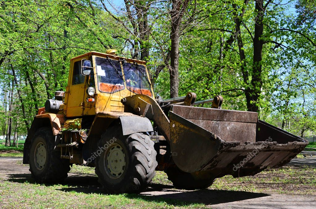 The city improvement team removes the fallen leaves in the park with an excavator and a truck. Regular seasonal work on improving the public places for recreation