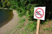 Fotografie Pilíř se znaménkem označující zákaz plavání. Znaménko ukazuje přeškrtnutý plovoucí osoba