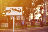 Fotografie A road sign that shows a car tow truck, which raises a passenger car on board
