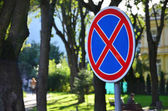 Fotografie Round road sign with a red cross on a blue background. A sign means a parking prohibition