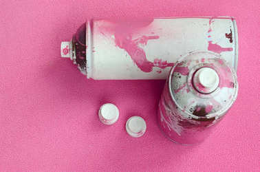 Some used pink aerosol spray cans and nozzles with paint drips lies on a blanket of soft and furry light pink fleece fabric. Classic female design color. Graffiti hooliganism concept