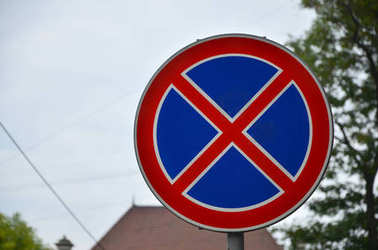 Round road sign with a red cross on a blue background. A sign means a parking prohibition