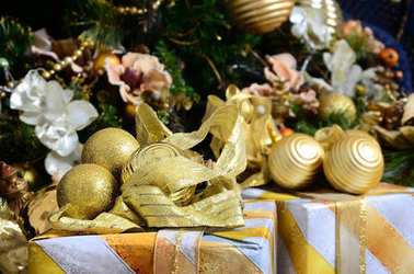Photo of luxury gift boxes under Christmas tree, New Year home decorations, golden wrapping of Santa presents, festive fir tree decorated with garland, baubles and toys, traditional celebration