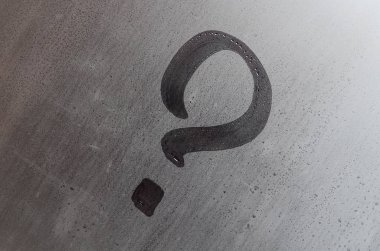 The inscription on glass, question mark concept. Question sign is painted on the surface of misted and wet window
