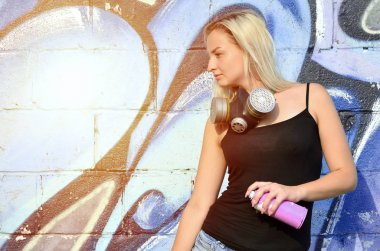 A young and beautiful sexy girl graffiti artist with a paint spray and gas mask on her neck stands on the wall background with a graffiti pattern in blue and purple tones